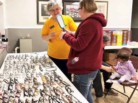 Optician Ranee King helps Rachael Ashbaugh pick out