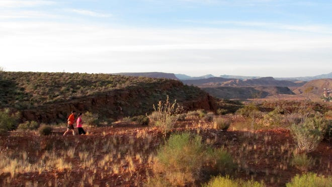 Karen Funk and Tony Ort participate in a group trail run on the Prospector Trail in the Red Cliffs Desert Reserve Wednesday, May 27, 2015.