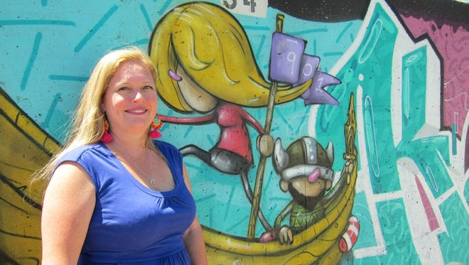 """Karen Golightly, co-founder and director of Paint Memphis, stands beside a panel painted by Memphis artists Lance Turner and Michael """"Birdcap"""" Roy."""