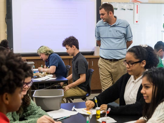 George Ennulat III walks around his classroom as he teaches an eighth-grade science class at Lodge Community School. Ennulat leads the class in a hands-on enrichment activity to measure the density of fluids by layering multiple salt solutions.