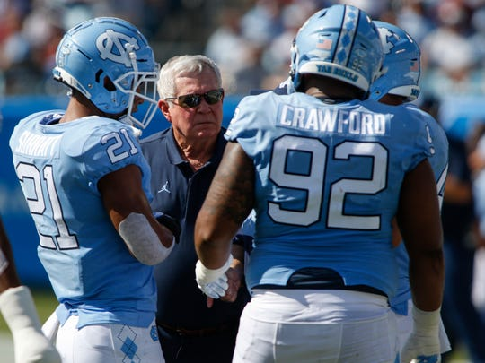 North Carolina coach Mack Brown talks to linebacker Chazz Surratt (21) and defensive lineman Aaron Crawford during their game against South Carolina.