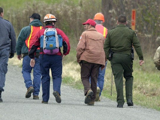 Members of a search party walk up Hagadorn Hill Road to search the property surrounding the home of Michele A. Harris in this November 2001 file photo. The Town of Spencer woman disappeared Sept. 11, 2001.