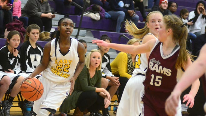 Hawkins Middle point guard Deshiya Hoosier dribbles around a screen set by Grace Doucette as Rucker-Stewart's Keely Gasterland defends during fourth-quarter action. Hoosier scored 24 points in the Lady Commandos' 45-38 victory.