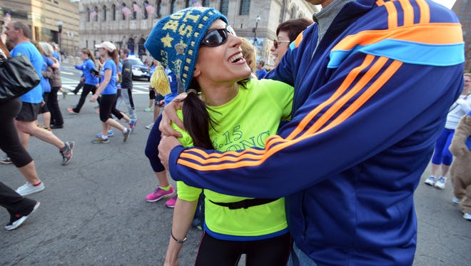 Lynn Crisci of Boston and Dave Fortier embrace near the finish line of the One Run for Boston on April 13, 2014.