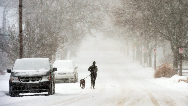 A jogger heads down Lions Park Drive through heavy snow Saturday, Jan. 13, 2018, in St. Joseph, Mich.