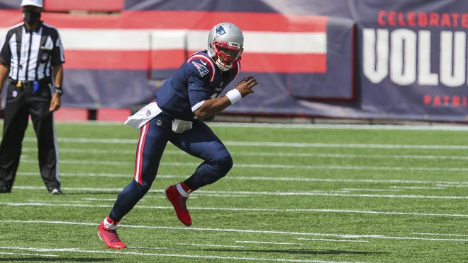 Patriots quarterback Cam Newton changes a play at the line of scrimmage during Sunday's game against the Dolphins. Because of his skill set, New England was able to use more option plays.