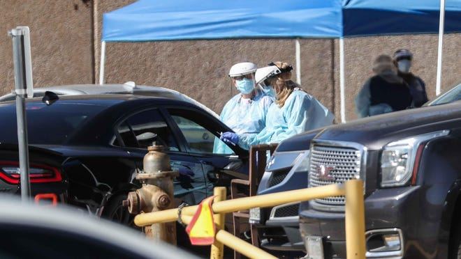 A medical staff member performs a COVID-19 test for the Austin school district on Nov. 16. The district on Sunday announced details for its post-Thanksgiving testing plan.