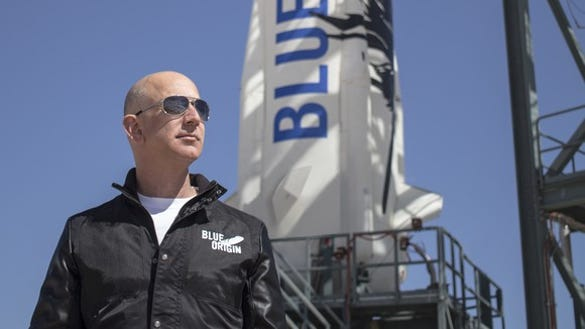 Jeff Bezos stands by a Blue Origin rocket.
