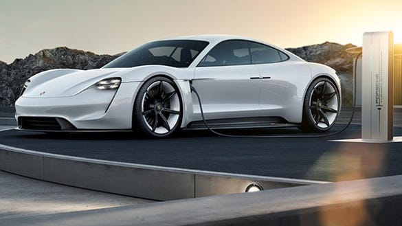 The Porsche Mission E concept vehicle, a futuristic-looking four-door, is shown at a recharging station.
