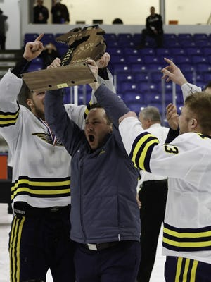 Hartland coach Rick Gadwa hoists the championship trophy after the Eagles beat Trenton, 4-2, in the Division 2 final at USA Hockey Arena on Saturday, March 10, 2018.