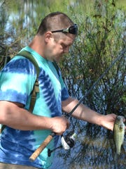 A foot-long largemouth bass was caught by Jason Wiggins of Hubbard while fishing in the shallows at Woodburn Pond.