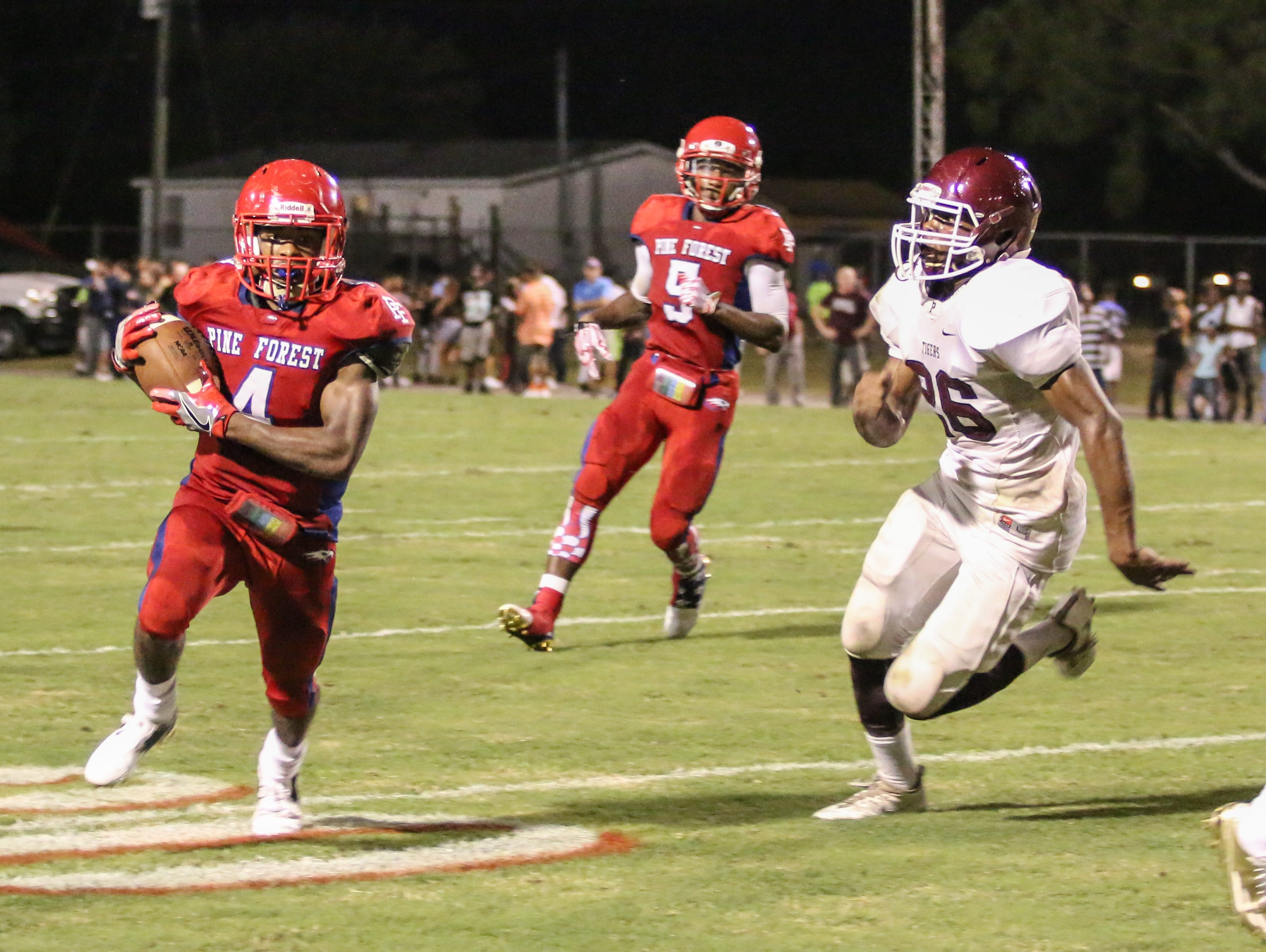 Pine Forest's Ladarius Wiggins (4) races outside past Pensacola's Devin Gadson (26) Friday night at Pine Forest High School.