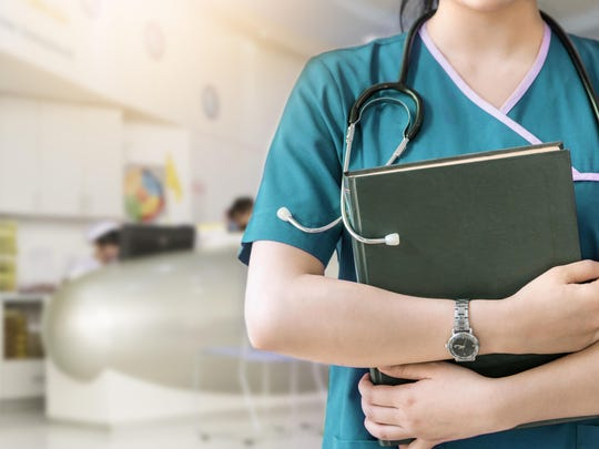 Cropped image of nurse holding green book on white background