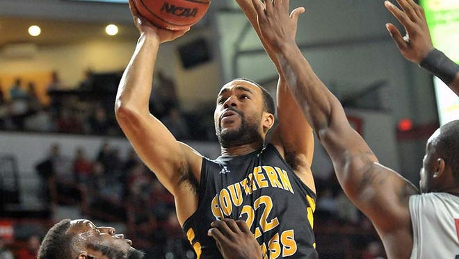 This Dec. 18, 2013 photo shows Southern Miss Golden Eagles forward Aaron Brown (22) shooting against Western Kentucky Hilltoppers guard T.J. Price (52).