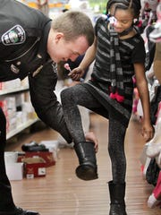 """Taylor Mill Police officer Daniel Potts helps Amani Mullins, 7, of Park Hills, get her boot back on after she tried on shoes  during the Kenton County Fraternal Order of Police Lodge 20 """"Cops and Kids"""" Christmas shopping program at Wal Mart, Fort Wright."""