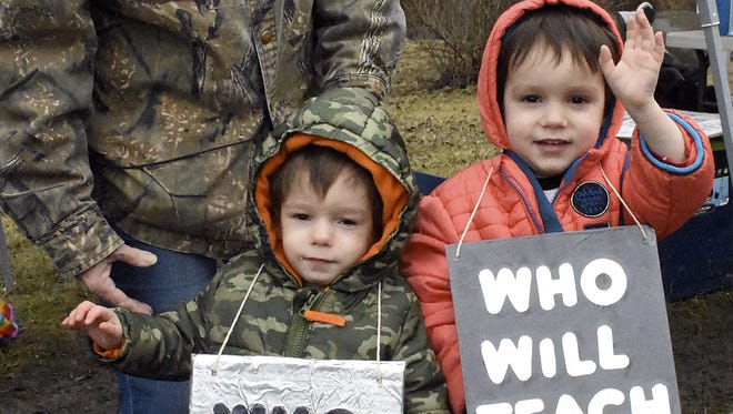 Twins, Corbin and Cameron Myers, 3, wave to supporters that honk as they past the teachers protest near North Marion High School, in Rachel, W.Va., Feb. 22, 2018.