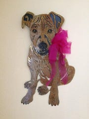 """A handcrafted metal wall hanging of a dog is made by by Dadra Hunt of Scottsdale, Ariz. """"I have worked with a lot of mediums but feel metal art resonates with me the most,"""" Hunt said. """"It's exciting to take something so seemingly hard and impassive and find the character within."""""""