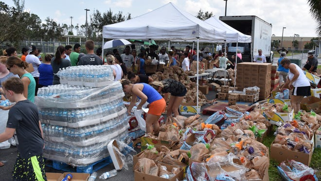 People stand in line to get food, water and other supplies at Parkside elementary in Naples.