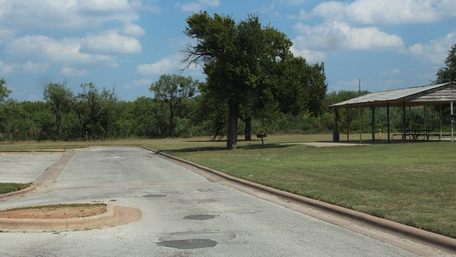 Decades after streets were improved at Kirby Park, roadways are full of potholes. Many of the trees around the pavilion are gone, as well as  playground equipment south of the structure.