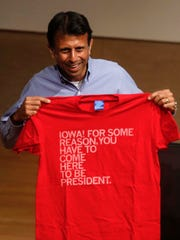 Louisiana Gov. and GOP presidential candidate Bobby Jindal holds up a Raygun t-shirt after he met with supporters on Friday, Oct. 30, 2015, at the State Historical building in Des Moines.