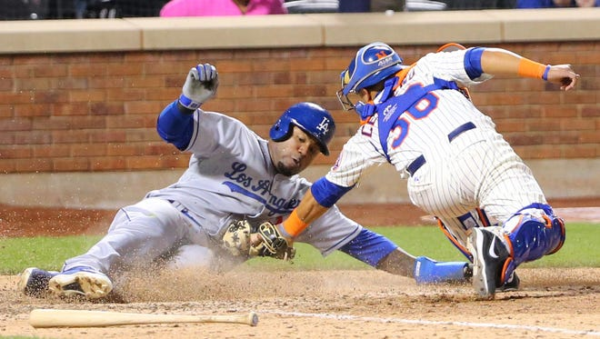 The Dodgers' Carl Crawford, left, slides safe as Mets catcher Juan Centeno fails to make the tag during the ninth inning at Citi Field on Tuesday.