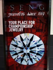 An elevator at the KFC Yum! Center advertises SENG jewelers as 'your place for championship jewelry.
