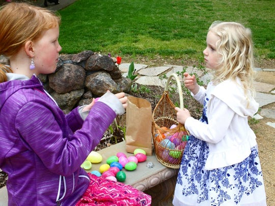 Children share candy and other treats at an egg hunt.