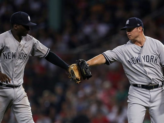 New York Yankees relief pitcher Zack Britton (53) (right) and shortstop Didi Gregorius (18) react after a great play by Didi Gregorius against the Boston Red Sox during the seventh inning at Fenway Park.