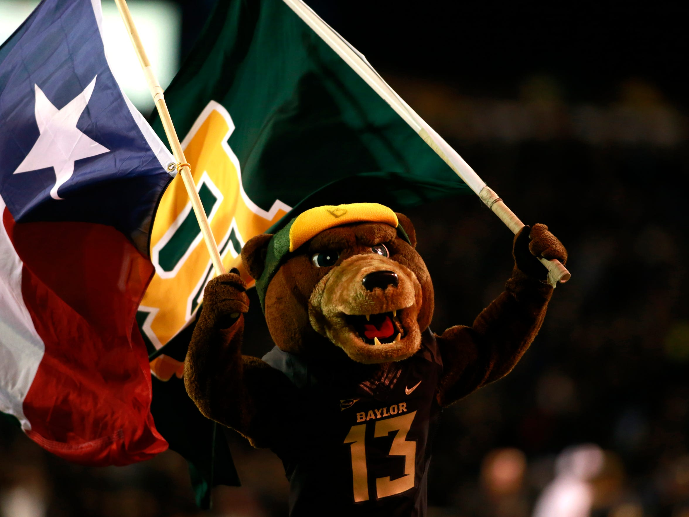 Baylor Bears mascot Bruiser runs on the field with a Texas state flag and a Baylor flag after a touchdown in the team's win against  Oklahoma on Nov. 7.