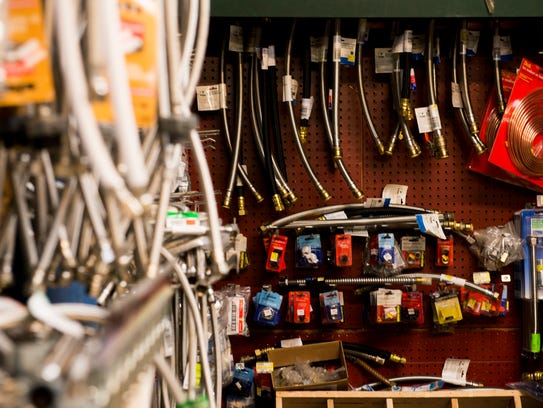 Pipe and plumbing materials line the walls of Hardware