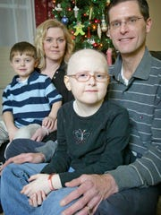 Olivia McTrusty, 6, sits with her father Lance, mother Lana, and brother Spencer, 4, in their living room Friday Dec. 28, 2007. Olivia, now 14, cut her hair for the first time Wednesday and is donating it to a charity that provides wigs to children with leukemia.