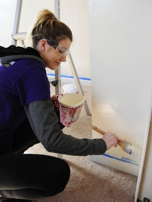 Volunteer Sabrina Behn paints around the trim at a Habitat for Humanity project home in Port Huron. Habitat recently received a $200,000 grant from the Stebbins Family Fund.