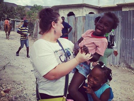 Kierstie Kirby poses with children in Haiti.