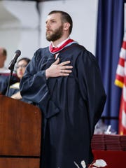 Then-Waukesha South High School Principal Ryan Galante covers his heart for the national anthem during South's commencement ceremony June 9, 2018. Galante faces two charges of child neglect in the injury of his 5-week-old daughter in December 2017. A trial is scheduled to begin May 21.