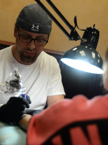 Tattoo artist Eric Hooven begins inking a tattoo on Heather Vinzinski, of Millville, memorializing a lost loved one her's, inside Synergy Tattoo Studio in Millville, Tuesday, Oct. 13.