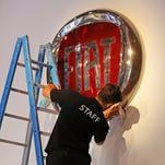 An employee cleans the Fiat logo, at the Paris Motor Show, in Paris, today.