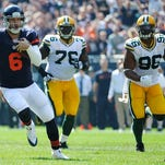 Bears quarterback Jay Cutler is chased by Mike Daniels (76) and Mike Neal (96) as he runs for a first down during the first quarter at Soldier Field.