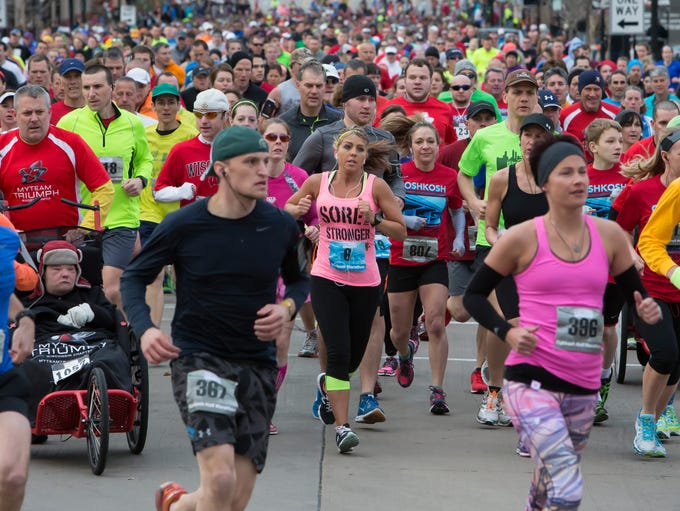 Runners start off on a packed Main Street in the Oshkosh