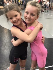 Kaleigh Kiesgen, left, and Rayna Richardson, right, wrestlers, then friends, and now, sisters.