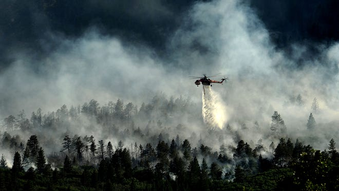 A helicopter drops water on the fire as firefighters continue to battle the blaze that burned into the evening hours in Waldo Canyon on the U.S. Air Force Academy in Colorado Springs, Colo., June 27, 2012.  Officials estimated that the fire had spread to about 10 acres of land belonging to the Academy. (U.S. Air Force photo/Master Sgt. Jeremy Lock)