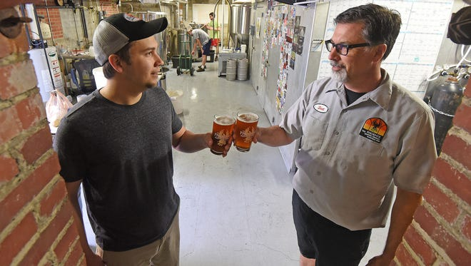 Phoenix Brewing Company co-owner Scott Cardwell and his son, assistant brewer Ian Cardwell, toast in the basement of the Phoenix Brewing Company on Thursday. The two collaborated on a Scottish ale together for Father's Day.