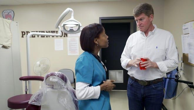 Missouri Democratic gubernatorial candidate Chris Koster, right, talks with Myrtle Hillard Davis Health Center dental director Carol Henley during a tour of the facility, Thursday in St. Louis.