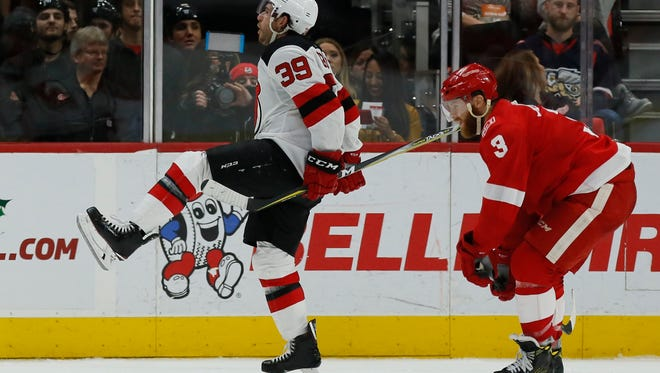 New Jersey Devils left wing Brian Gibbons (39) celebrates his winning goal in overtime as Detroit Red Wings defenseman Nick Jensen (3) skates past at an NHL hockey game Saturday, Nov. 25, 2017, in Detroit. (AP Photo/Duane Burleson)