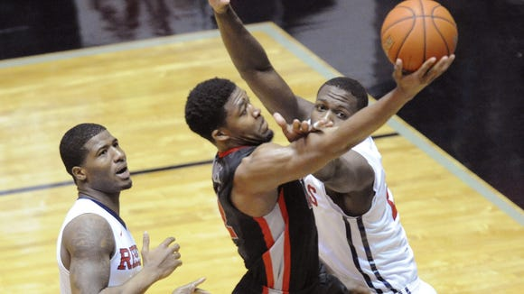Georgia guard Kenny Gaines (12) shoots against Mississippi guard Martavious Newby, left, and center Dwight Coleby during an NCAA college basketball game in Oxford, Miss., on Wednesday, Feb. 25, 2015. Georgia won 76-72. (AP Photo/Oxford Eagle, Bruce Newman)
