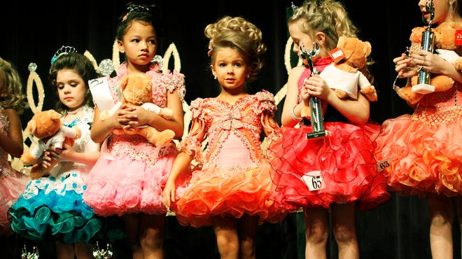 Karmen Walker, 6, center, competes in the Southern Celebrity Beauty pageant in Charleston, W. Va., in a scene from 'Toddlers and Tiaras' on TLC.