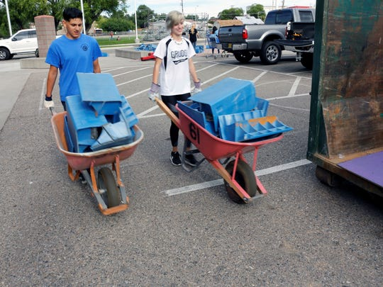 Nick Ritter, left, and Taylor Henson push wheelbarrows full of old bleacher seats to a trash bin outside the Boys & Girls Clubs of Farmington on Tuesday.