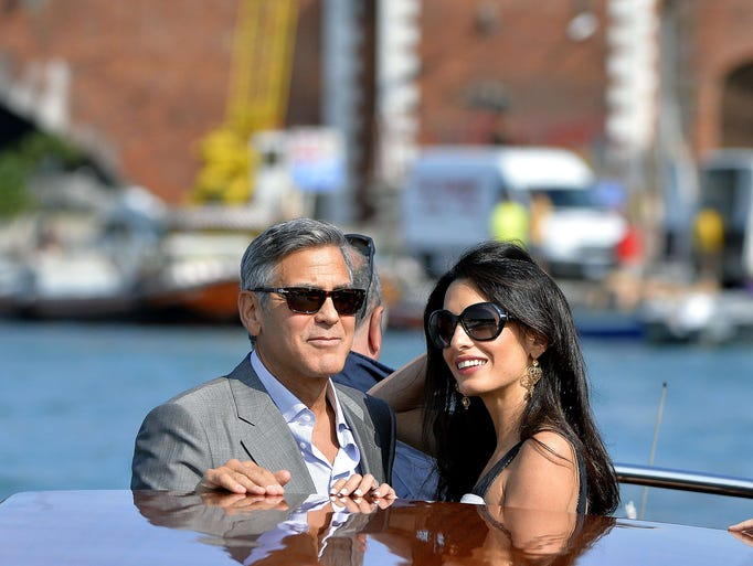 George Clooney and his fiancee Amal Alamuddin take a taxi boat upon their arrival in Venice on September 26, 2014, on the eve of their wedding.