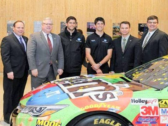 Assemblyman Philip Palmesano (left), Senator Tom O'Mara, Jordan Taylor, Ricky Taylor, Assemblyman Chris Friend, and WGI Vice President of Business Development and Partnerships Jon Beckman, in front of the Kyle Busch Sprint Cup car at the Empire State Plaza in Albany.