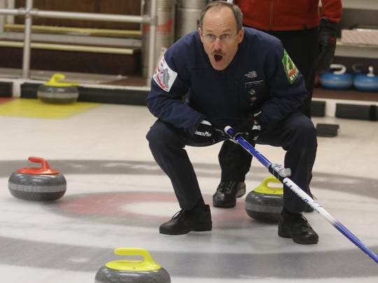 Link Heffner of Clinton gives directions to his team's sweepers to clear ice, helping the stone reach its target.