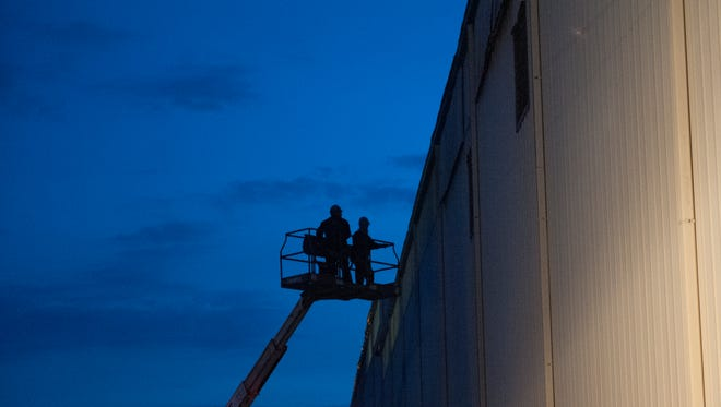 Two workers open building vents on the side of Glen-Gery Brick plant in Iberia to help clear out the lingering smoke from a fire that occurred Monday night in an air compressor room.